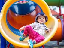 Gelukkige meisje het spelen schuif bij de speelplaats Kinderen, Ha stock foto's