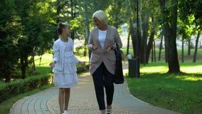 Gelukkige meisje het vertellen verhalen aan grootmoeder het lopen in park, het vertrouwen op relaties stock footage