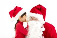 Gelukkige Meisje het vertellen wens in het oor van Santa Claus ` s Stock Foto