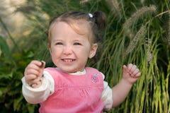 Gelukkige meisjepeuter die excitedly met een kiezelsteen pronkt. Royalty-vrije Stock Fotografie