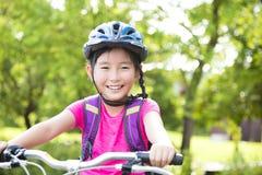 Gelukkige meisjes berijdende fiets in het park royalty-vrije stock fotografie