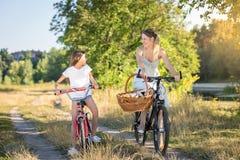 Gelukkige meisjes berijdende fiets met haar moeder in weide bij zonsondergang Stock Afbeeldingen