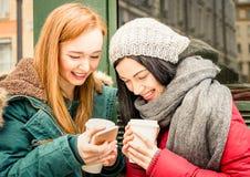 Gelukkige meisjes beste vriend die pret met koffie en telefoons hebben royalty-vrije stock foto
