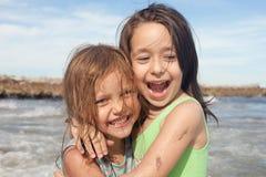Gelukkige meisjes bij het strand Stock Foto