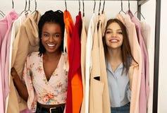 Gelukkige meisjes bij wekelijkse doekmarkt, hebbend pret en samen winkelend stock fotografie