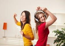 Gelukkige meisjes die aan muziek dansen Stock Fotografie