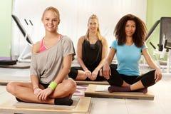 Gelukkige meisjes die bij de gymnastiek rusten Stock Afbeeldingen