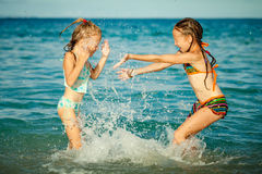 Gelukkige meisjes die bij het strand spelen Stock Fotografie