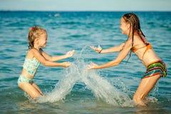 Gelukkige meisjes die bij het strand spelen Stock Foto's