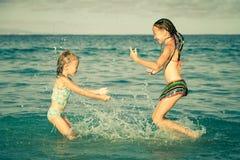 Gelukkige meisjes die bij het strand spelen Royalty-vrije Stock Afbeeldingen