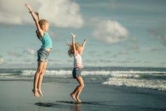 Gelukkige meisjes die bij het strand springen Stock Afbeeldingen