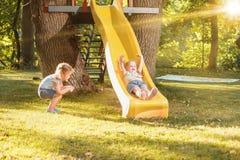 Gelukkige meisjes die de heuvel op de speelplaats naar beneden rollen Stock Fotografie