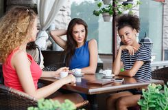 Gelukkige meisjes die in de koffie en het spreken zitten Stock Afbeelding