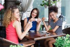 Gelukkige meisjes die in de koffie en het spreken zitten Royalty-vrije Stock Foto
