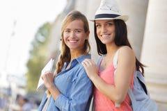 Gelukkige meisjes die door stad tijdens vakantie lopen Stock Foto's
