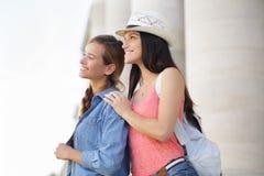 Gelukkige meisjes die door stad tijdens vakantie lopen Royalty-vrije Stock Afbeeldingen
