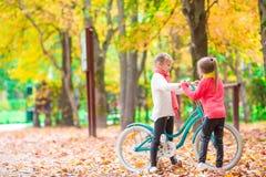 Gelukkige meisjes die een fiets in openlucht berijden bij mooie de herfstdag Royalty-vrije Stock Fotografie