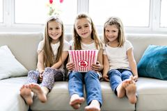 Gelukkige meisjes die komedie op film op TV letten en popcorn thuis eten royalty-vrije stock fotografie