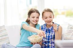 Gelukkige meisjes die met popcorn op TV thuis letten Stock Afbeelding