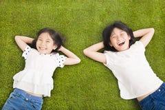 Gelukkige Meisjes die op het gras rusten stock foto's