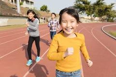 Gelukkige meisjes die op het spoor lopen stock foto