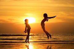 Gelukkige meisjes die op het strand springen Stock Afbeeldingen