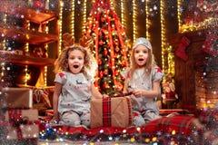 Gelukkige meisjes die open de giftdoos dragen van Kerstmispyjama's door een open haard in een comfortabele donkere woonkamer op K royalty-vrije stock fotografie