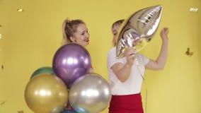 Gelukkige meisjes die partij hebben en op gele achtergrond dansen stock video