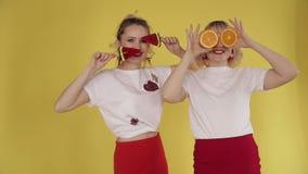 Gelukkige meisjes die partij hebben en op gele achtergrond dansen stock footage