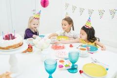 Gelukkige meisjes die in partijkappen suikergoed eten bij verjaardagspartij stock afbeelding