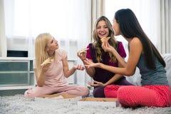Gelukkige meisjes die pizza thuis eten Stock Foto
