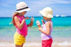 Gelukkige meisjes die roomijs over de achtergrond van het de zomerstrand eten Mensen, kinderen, vrienden en vriendschapsconcept Stock Foto's