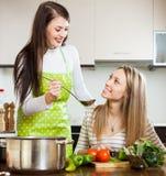 Gelukkige meisjes die thuis keuken koken stock foto