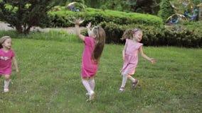 Gelukkige meisjes die in tuin en het spelen bellen spelen stock video