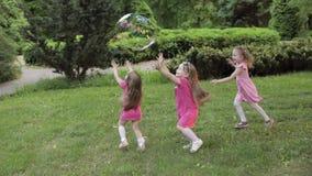 Gelukkige meisjes die in tuin en het spelen bellen spelen stock footage