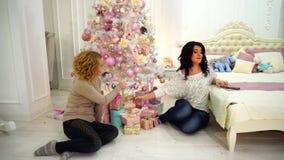 Gelukkige meisjes die voor viering die van Kerstmis voorbereidingen treffen, op vloer in heldere slaapkamer met feestelijke binne stock footage