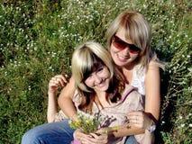 Gelukkige meisjes met bloemen Royalty-vrije Stock Afbeeldingen