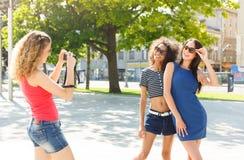 Gelukkige meisjes met camera in openlucht in de stad stock afbeelding