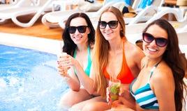 Gelukkige meisjes met dranken op de zomerpartij dichtbij de pool, de zomer stock afbeeldingen