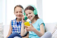 Gelukkige meisjes met smartphone en hoofdtelefoons Royalty-vrije Stock Afbeeldingen