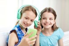 Gelukkige meisjes met smartphone en hoofdtelefoons Stock Fotografie