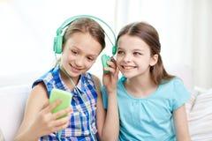 Gelukkige meisjes met smartphone en hoofdtelefoons Royalty-vrije Stock Foto