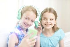 Gelukkige meisjes met smartphone en hoofdtelefoons Stock Foto