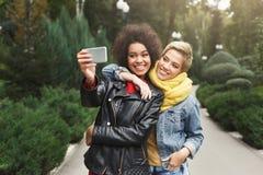 Gelukkige meisjes met smartphone in openlucht in het park Stock Foto's