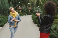 Gelukkige meisjes met smartphone in openlucht in het park stock afbeelding