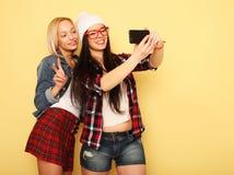 Gelukkige meisjes met smartphone over gele achtergrond Gelukkige zelf Stock Foto