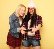 Gelukkige meisjes met smartphone over gele achtergrond Gelukkige zelf Stock Afbeelding