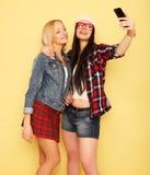 Gelukkige meisjes met smartphone over gele achtergrond Gelukkige zelf Royalty-vrije Stock Afbeelding