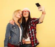 Gelukkige meisjes met smartphone over gele achtergrond Gelukkige zelf Royalty-vrije Stock Foto