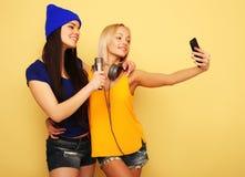 Gelukkige meisjes met smartphone over gele achtergrond Gelukkige zelf Royalty-vrije Stock Foto's